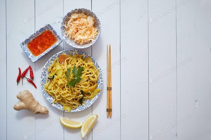 Leckere und frische Nudeln mit Huhn und Gemüse serviert auf Keramikplatte mit Stäbchen
