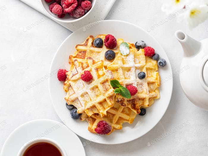 Belgian waffles with raspberries, blueberries, curd and tea, top view. Healthy homemade
