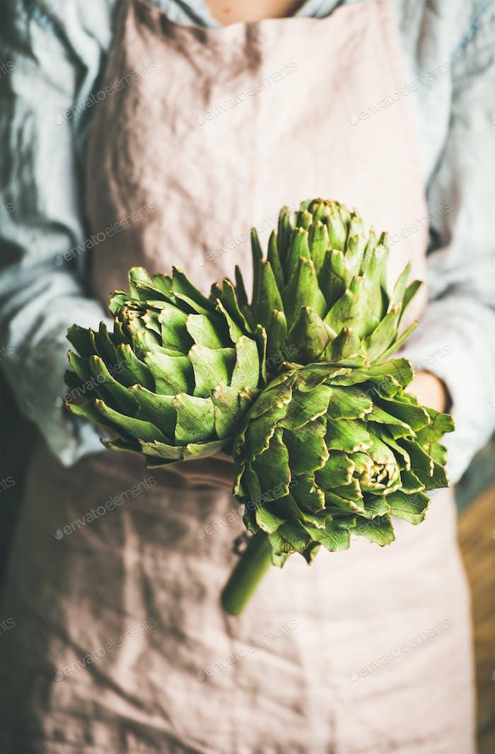 Female farmer in apron holding fresh artichokes