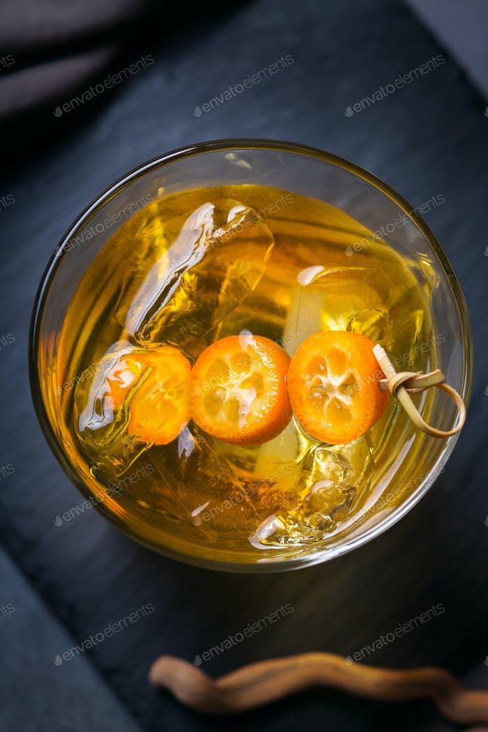 Glas starken Alkohol, Whisky, Eis, Kumquat auf einem Tisch