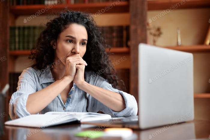 Tired lady sitting at desk with laptop