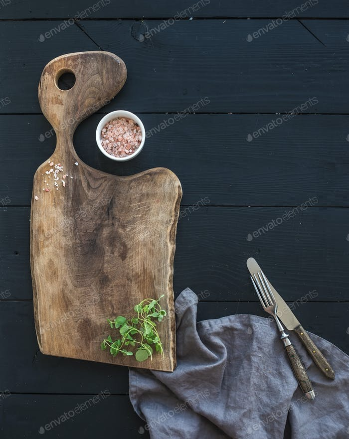 Kitchen-ware set. Old rustic chopping board made of walnut wood, salt and oregano herb