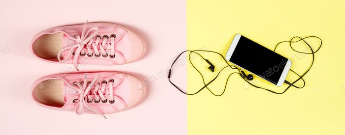Pink canvas sneakers and mobile phone, close up