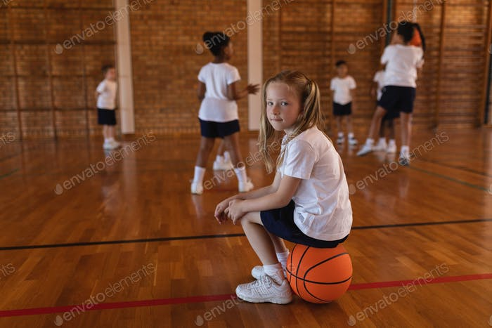 Side view of schoolgirl sitting on basketball and looking at camera at basketball court in school