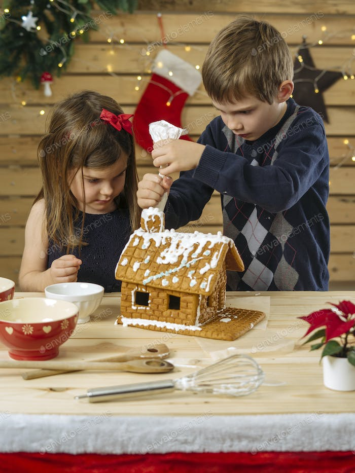 Brother and sister decorating gingerbread house