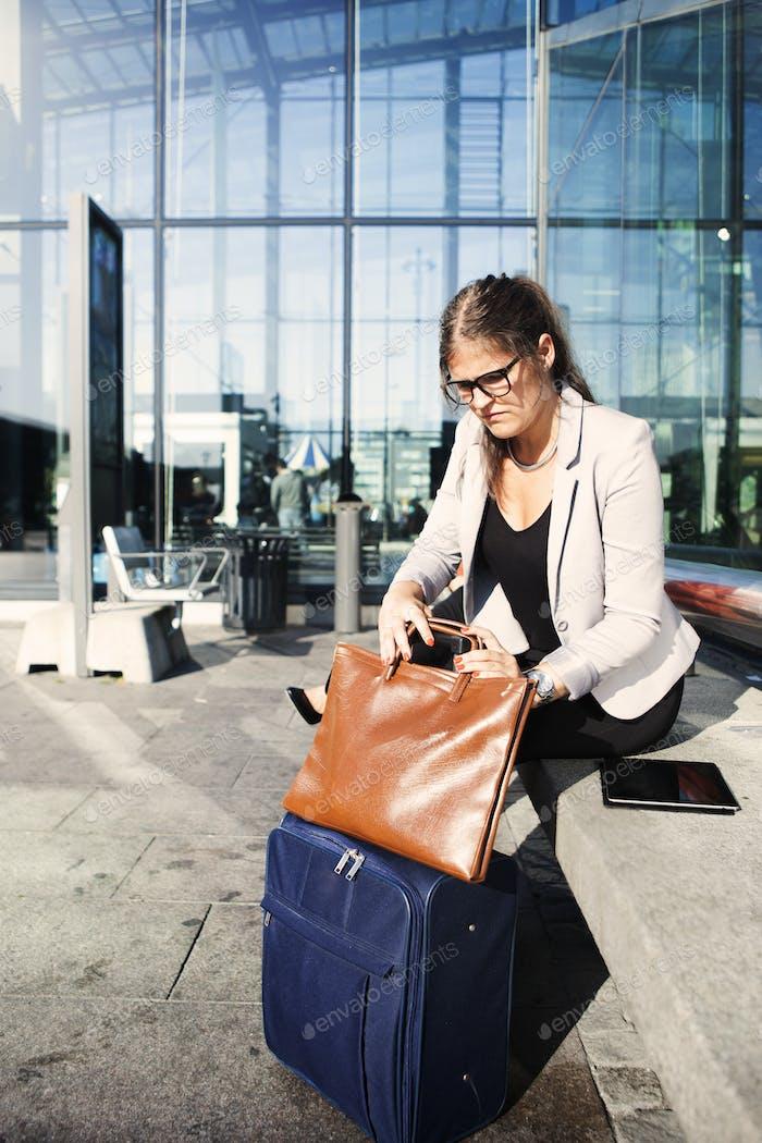 Geschäftsfrau Blick auf Geldbörse beim Sitzen außerhalb Bahnstation
