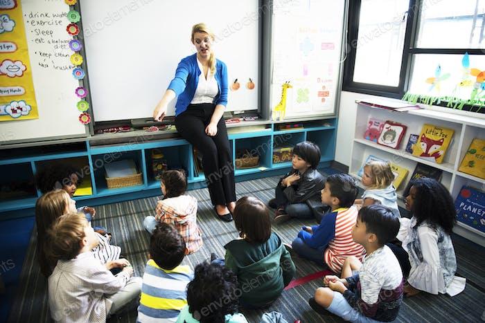 Kindergarten-Studenten sitzen auf dem Boden hören Lehrer
