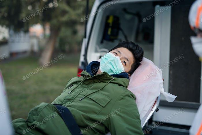 Man on stretcher by ambulance outdoors, coronavirus concept