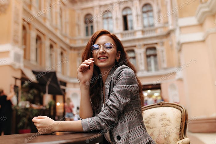 Attractive woman in plaid outfit and eyeglasses sitting in city cafe