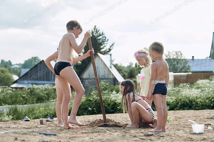 Small children play in the sand in the yard of their house in the summer.