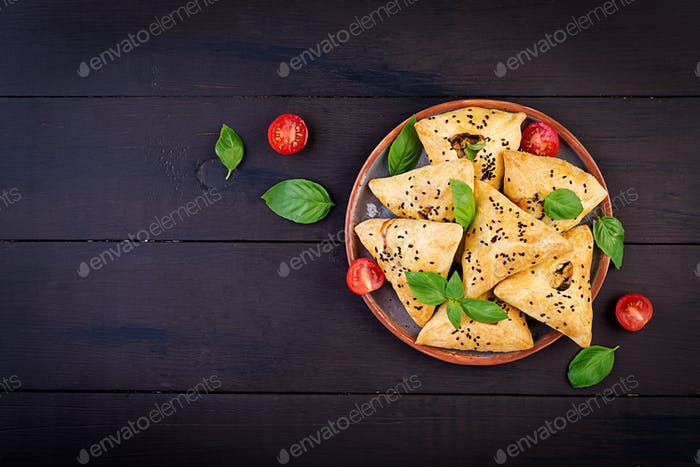 Asian food. Samsa (samosa) with chicken fillet and green herbs on wooden background. Top view