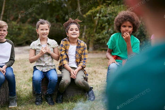 Children On Outdoor Activity Camping Trip Sit Around Camp Fire Together