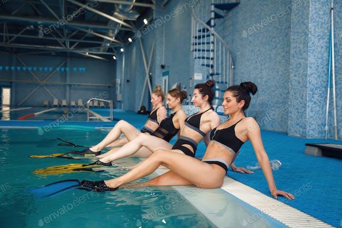 Schwimmer Gruppe in Flossen am Pool