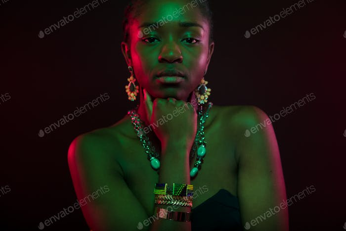 Woman With Hand On Chin Wearing Jewelry Over Black Background