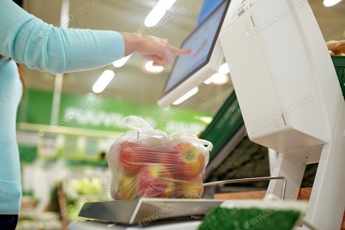 Frau mit einem Gewicht von Äpfeln auf der Waage im Lebensmittelgeschäft
