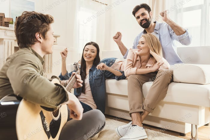 Diverse people partying together at dining room, playing acoustic guitar