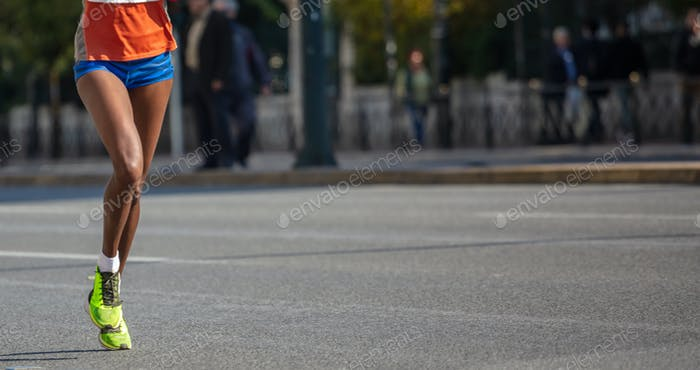 Running in the city roads. Young woman runner, front view, banner, blur background