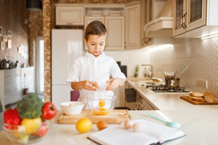 Litte boy stirs raw eggs in a bowl