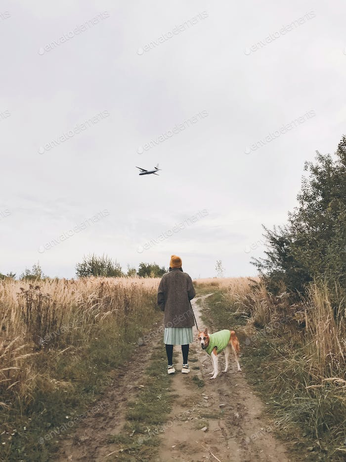 Stylish Hipster girl in yellow hat and coat walking with her golden dog and looking at plane