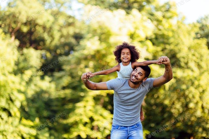 Porträt von jungen Vater trägt seine Tochter auf dem Rücken