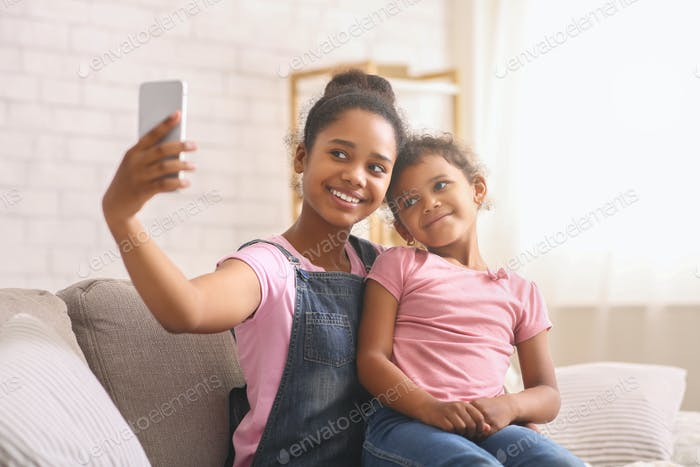 African teen girl taking selfie with her baby sister