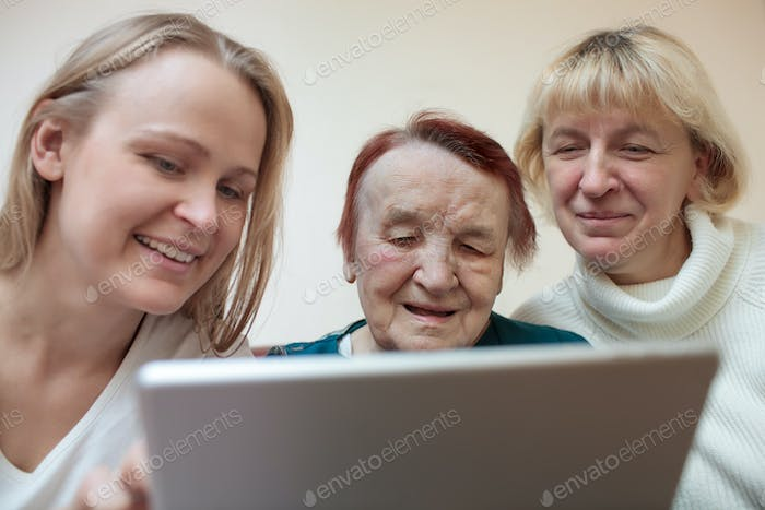 Three women using a smart tablet