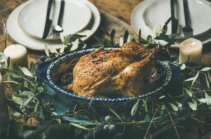 Whole roasted chicken decorated with olive tree branch, selective focus