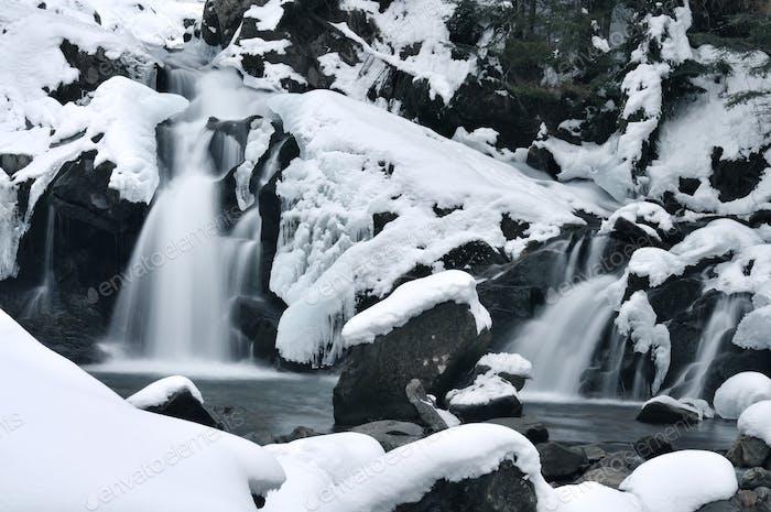 Beautiful mountain waterfall covered in ice