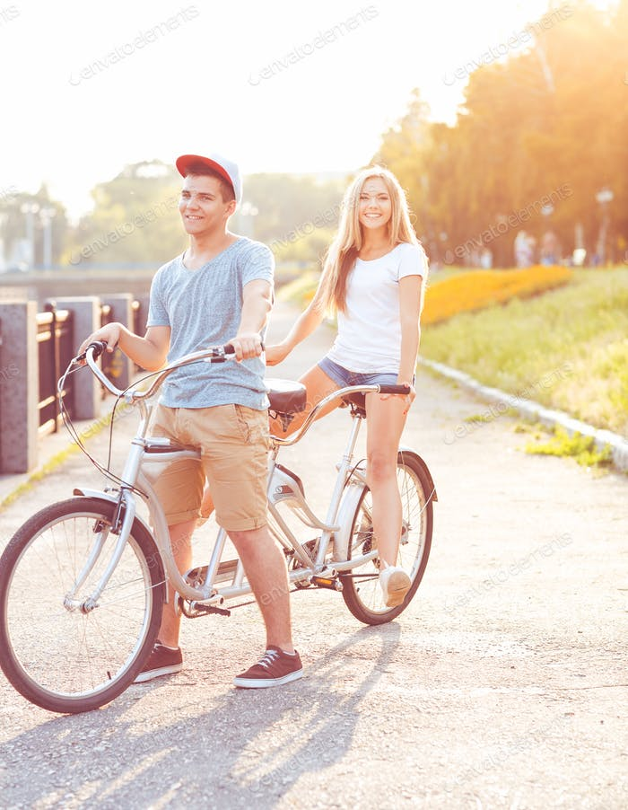 Happy couple riding a bicycle in the park outdoors