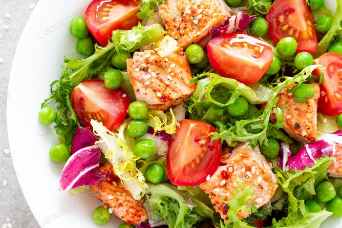 Healthy lunch vegetable salad with baked salmon fish, fresh green peas, lettuce and tomato. Top view
