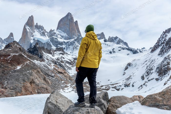 A hiker with a yellow jacket on the base of Fitz Roy Mountain in Patagonia, Argentina