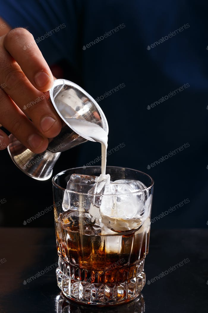 Bartender prepares a white russian cocktail