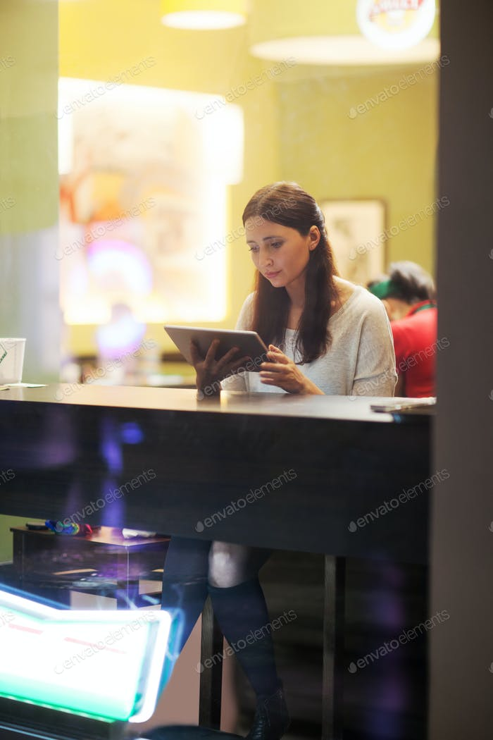 Young brunette girl using tablet in the cafe