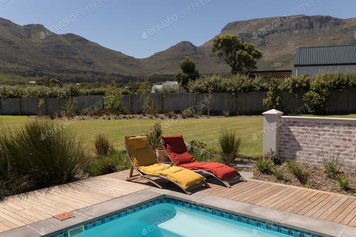 Empty sun lounger chairs placed next to the swimming pool at the backyard of home