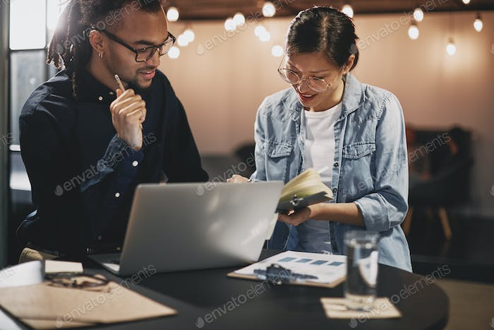 Diverse colleagues smiling and going over notes in an office