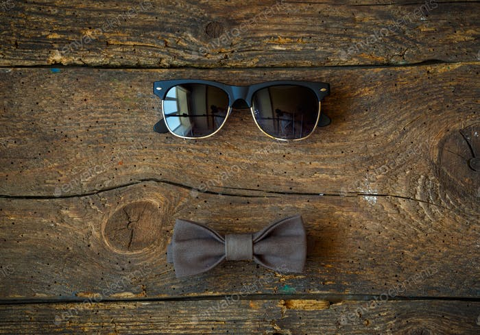 Sunglasses and bow tie on a wooden background