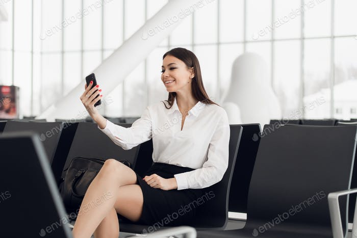 Young business woman at international airport, making selfie with mobile phone