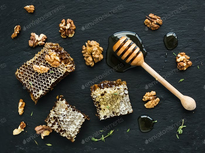 Honeycomb, walnuts and honey dipper on black slate tray over grunge dark backdrop