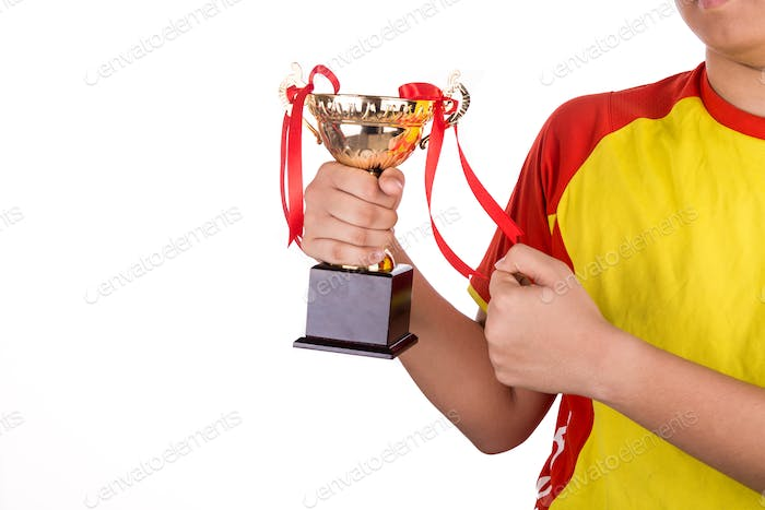 Proud athlete gestures with firm fist whilst holding gold trophy