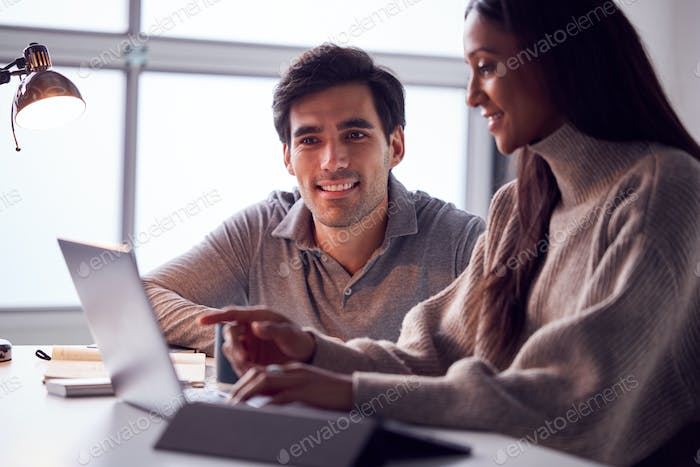 Businesswoman Working On Laptop At Desk Collaborating With Male Colleague