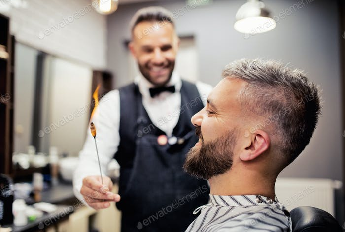 Hipster man client visiting haidresser and hairstylist in barber shop, ear hair removal.
