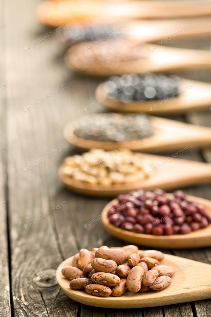 verschiedene getrocknete Hülsenfrüchte in Holzlöffel
