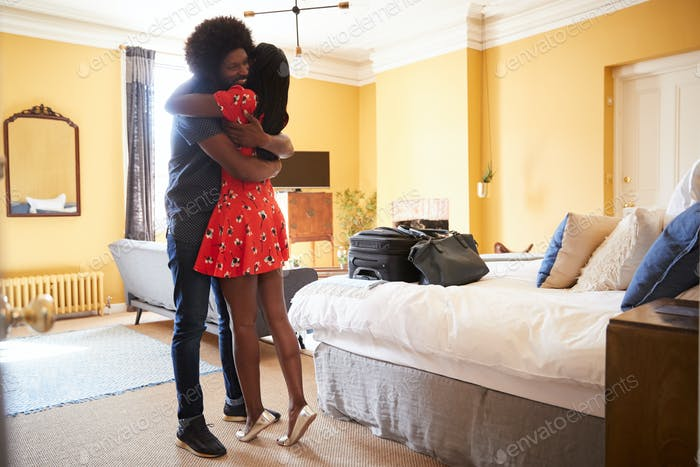 Black couple embracing in a hotel room, full length close up