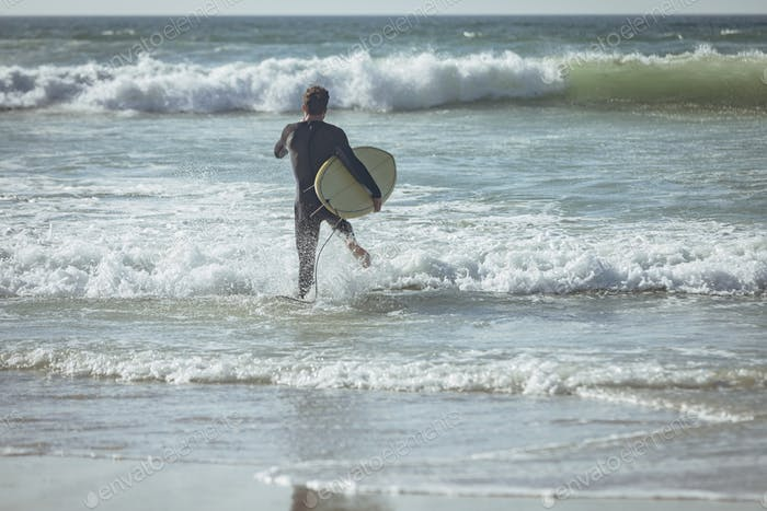 Rear view of young Caucasian male surfer with a surfboard running on a beach