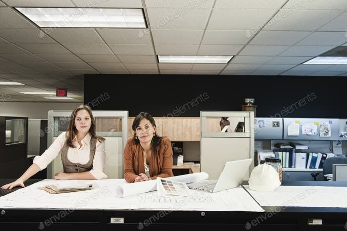 Mixed race and Caucasian females working on a project at a table in their office.