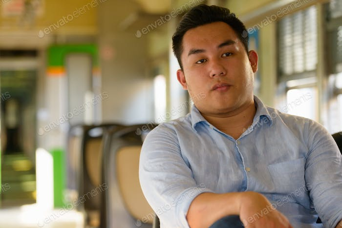 Young overweight Asian tourist man inside the train