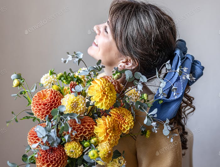 A pretty young woman holds a bouquet of chrysanthemums.