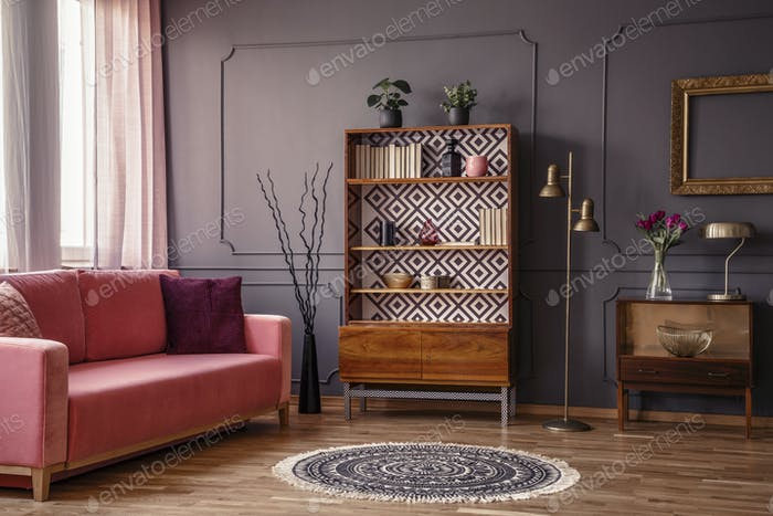 Antique wooden bookcase with decorations in an elegant gray livi