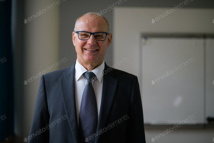 Happy Senior Businessman Smiling By The Window In The Office