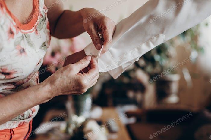 Mutter helfende Bräutigam setzen auf Manschettenknöpfe